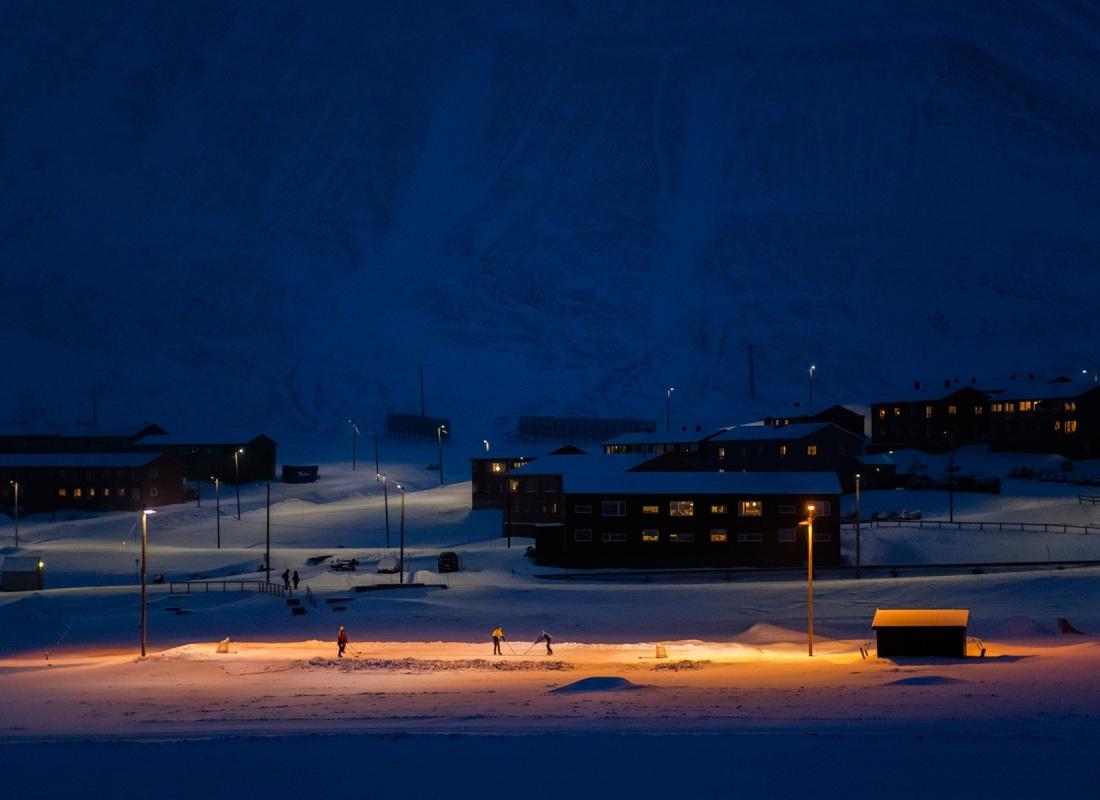 Sulle Isole Svalbard c'è la scuola e centinaia di bambini, coloni figli di coloni.  Qui, un pomeriggio che volge al buio, al termine della ora blu, tre bambini giocano su un campo da hockey improvvisato.